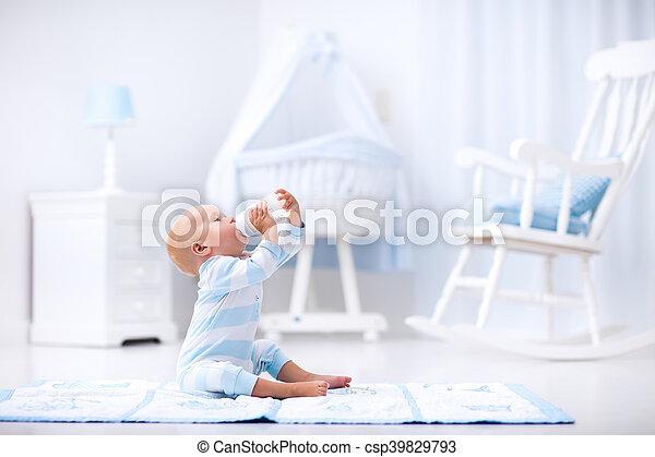 Baby boy drinking milk in sunny nursery - csp39829793