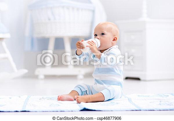 Baby boy drinking milk in sunny nursery - csp46877906