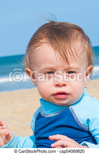 1eefe5a38 Baby boy playing at the beach. Baby boy wearing blue shirt playing ...