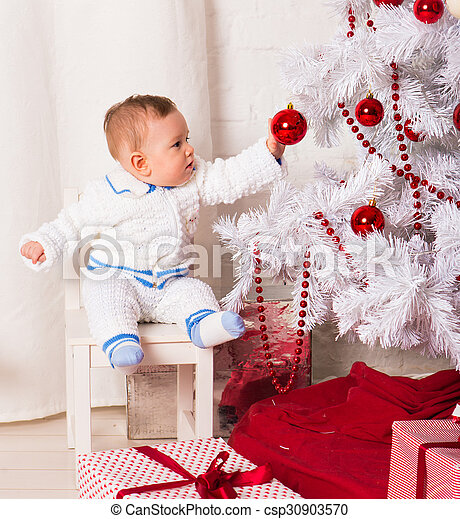baby boy playing with Christmas tree decoration - csp30903570