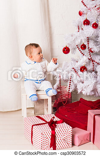baby boy playing with Christmas tree decoration - csp30903572