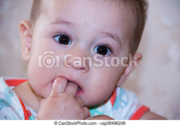 Baby boy plays with fingers in mouth and happy facial expression. Portrait of a crawling smiling. Teething infant playing. Newborn child at home. The scratching his teeth. - csp38496248