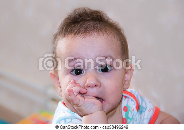 Baby boy plays with fingers in mouth and happy facial expression. Portrait of a crawling smiling. Teething infant playing. Newborn child at home. The scratching his teeth. - csp38496249