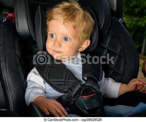 Baby boy sitting in a car seat. Infant