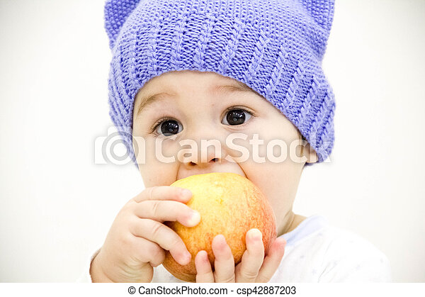 baby boy sitting on table with fruits and vegetables and eating an apple isolated on white background - csp42887203