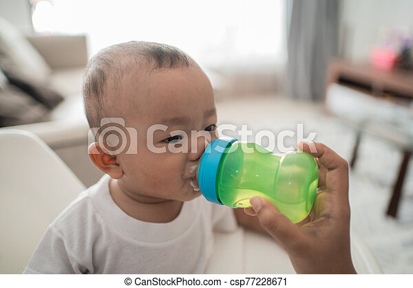 baby boy sucking bottle of water - csp77228671