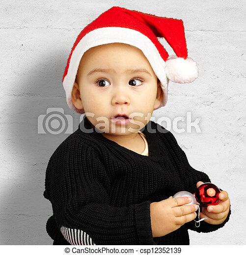 72b191a84e74f Baby boy wearing santa hat holding christmas ornaments against a ...