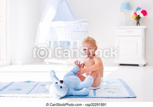 Baby boy with milk bottle in sunny nursery - csp32291891