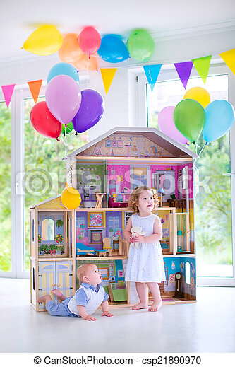 Baby brother and sister playing with a doll house - csp21890970
