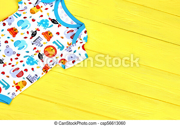 58ca0b439 Baby cute romper, copy space. infants fancy design bodysuit on colored wooden  background. newborn apparel on sale.
