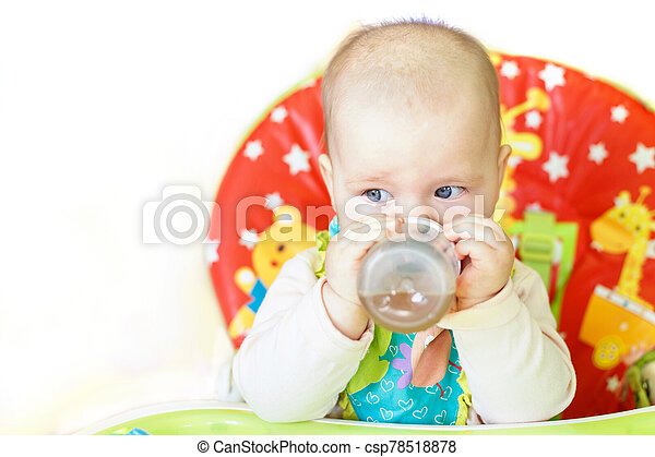 baby drinking from bottle sitting in high chair on a white background - csp78518878