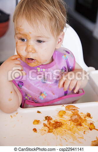 baby eating tomato meal with her hand - csp22941141