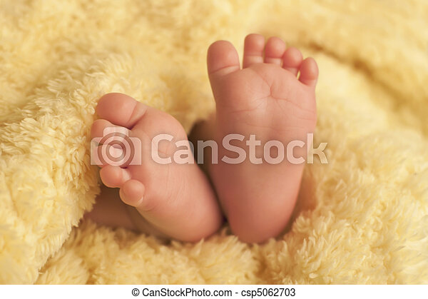 Baby feet on yellow blanket - csp5062703