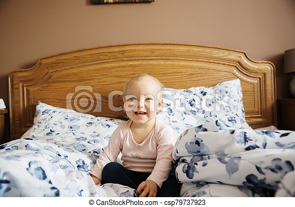 baby girl in the parents bed - csp79737923