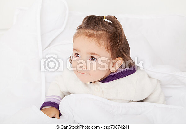 baby girl is hiding under the white blanket - csp70874241