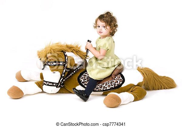 Baby girl on stuffed animal horse - csp7774341