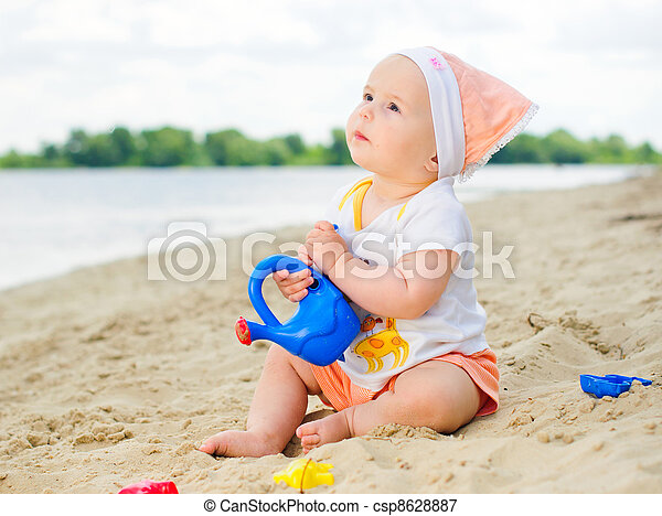 baby girl playing on the beach with sand. - csp8628887