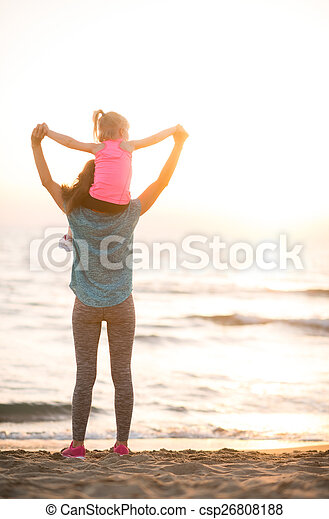 Baby girl sitting on shoulders of mother and rejoicing while on  - csp26808188