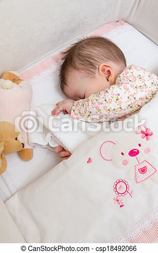 Baby girl sleeping in a cot with pacifier and toy - csp18492066
