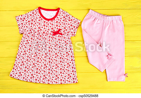 80d907b1e Baby-girl summer cotton clothes. toddler girl beautiful printed top and  pink leggings on yellow wooden background, top view.