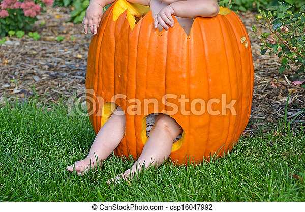 baby in carved pumpkin - csp16047992