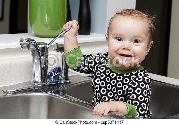 Baby in kitchen sink. Baby sitting in kitchen sink playing ...