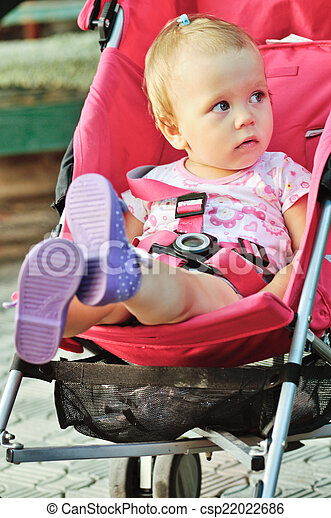 baby  in red stroller - csp22022686