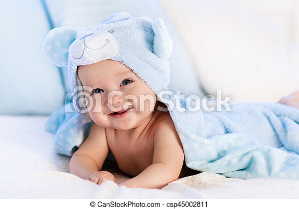 Baby in towel after bath in bed. Baby boy wearing diaper and ...