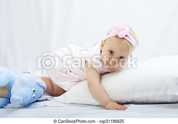 baby is playing with pillow over white background - csp31186625