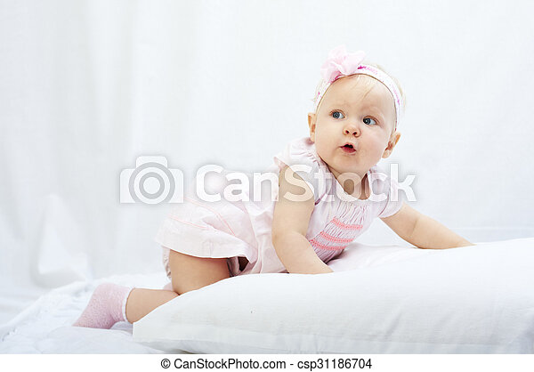 baby is playing with pillow over white background - csp31186704