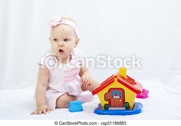 baby is playing with toys over white background - csp31186883