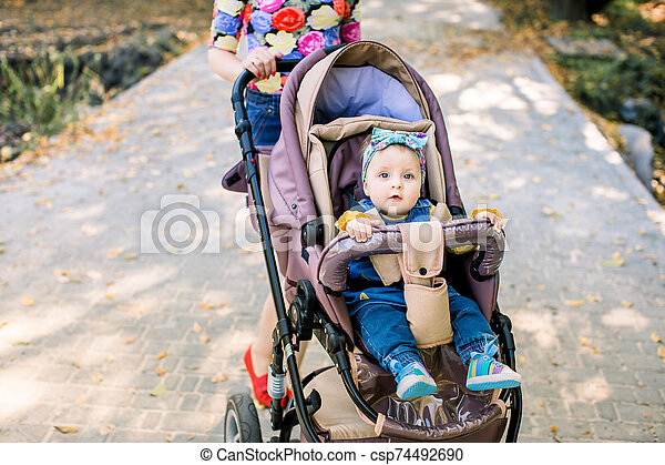 baby is sitting on carriage alone. Baby in sitting stroller on nature - csp74492690