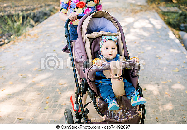 baby is sitting on carriage alone. Baby in sitting stroller on nature - csp74492697