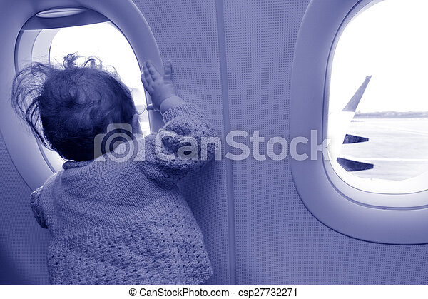 Baby looks out from airplane window  - csp27732271