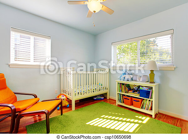 Baby nursery room design with green rug, blue walls and orange chair. - csp10650698