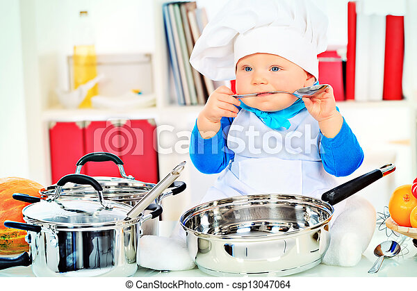 d2aece282 Baby nutrition. Cute small baby in the cook costume at the kitchen.