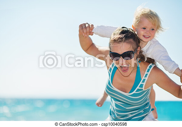Baby piggybacking mother on beach - csp10040598