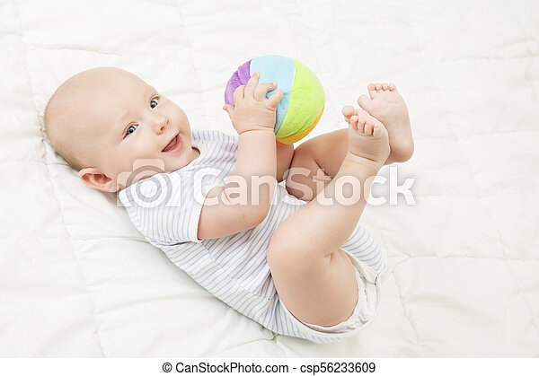Baby Play Toy Ball, Happy Kid Lying on Back Playing Soft Toys, Infant Child Lie on White Blanket - csp56233609