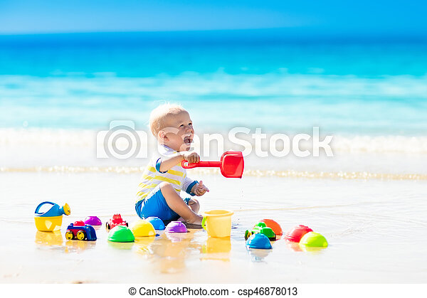 Baby playing on tropical beach digging in sand - csp46878013