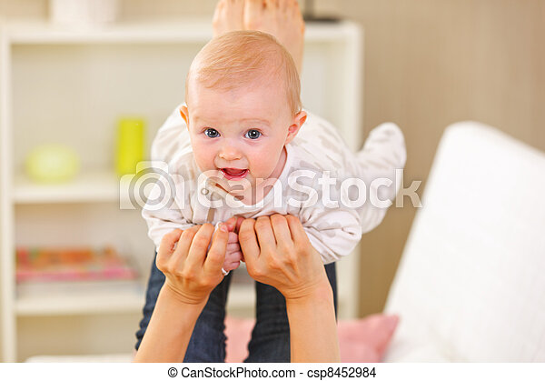 Baby playing with mother at home - csp8452984