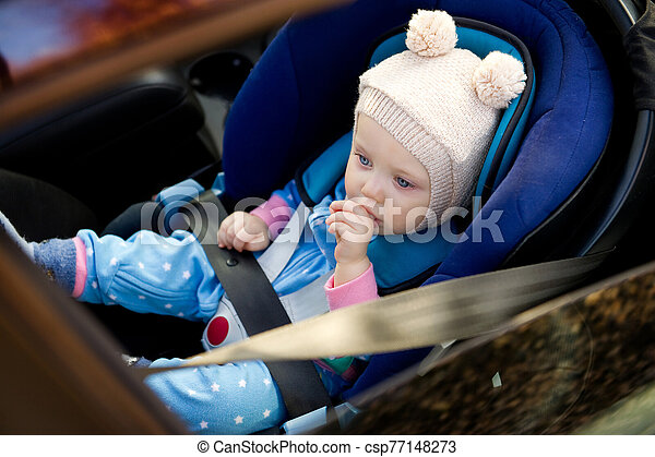 baby sitting in a car seat - csp77148273