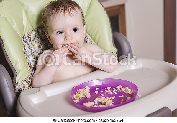 baby sitting in high-chair eating with her hand - csp29493754
