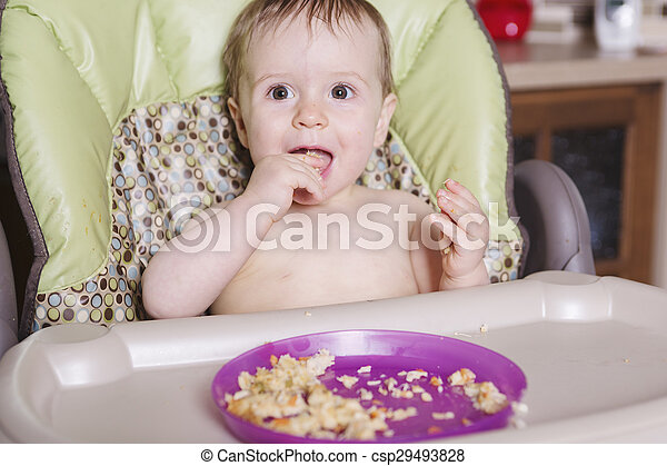 baby sitting in high-chair eating with her hand - csp29493828