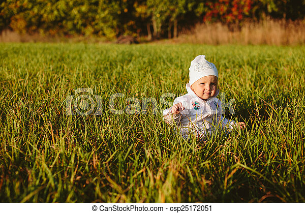 baby sitting in the grass - csp25172051