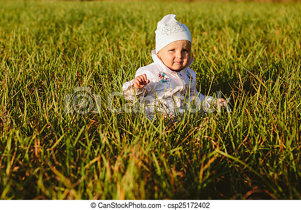 baby sitting in the grass - csp25172402