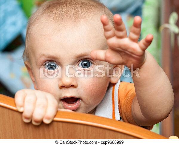 Baby standing in crib - csp9668999