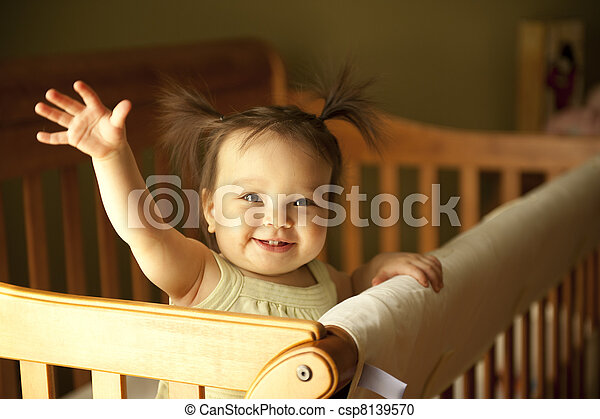 Baby standing up in crib - csp8139570