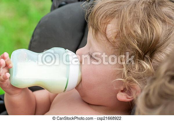 baby sucking on a bottle of porridge sitting in a wheelchair - csp21668922