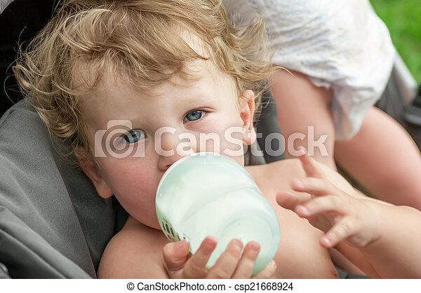 baby sucking on a bottle of porridge sitting in a wheelchair - csp21668924