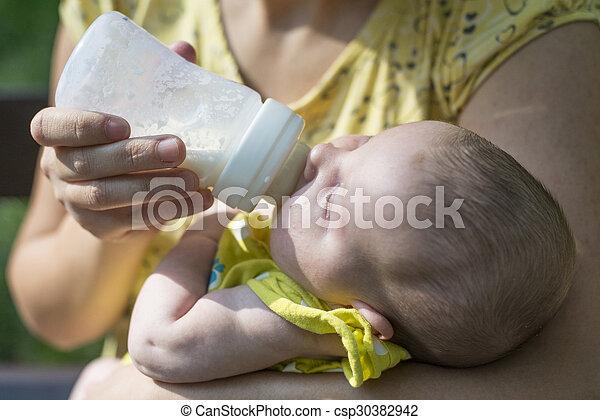 Baby sucks on a bottle - csp30382942
